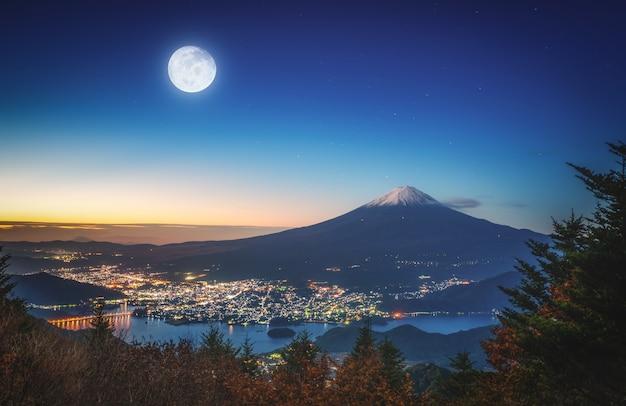 Mt. fuji over lake kawaguchiko met herfstbladeren en fullmoon bij zonsopgang in fujikawaguchiko, japan.