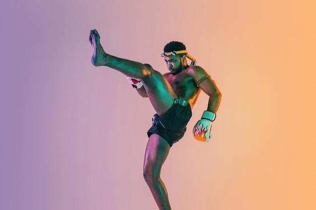 Muay thai. jonge man die thai boksen uitoefent op gradiëntmuur in neonlicht. vechter oefenen, training in vechtsporten in actie, beweging. gezonde levensstijl, sport, aziatisch cultuurconcept.