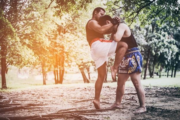 Muay thai krijgskunst of thai boksen, twee jonge kickbox jagers trainen in het park