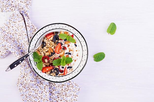 Muesli, aardbeien, kers, kamperfoeliebes, noten en yoghurt in een kom