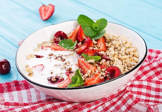 Muesli, aardbeien, kersen, noten en yoghurt in een kom op een houten tafel