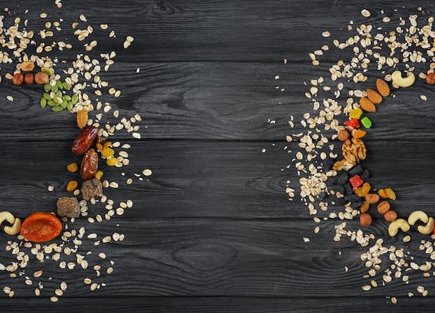 Muesli. havermout verspreid in een cirkel, gedroogde vruchten, noten, rozijnen, zaden, op een houten gestructureerde achtergrond