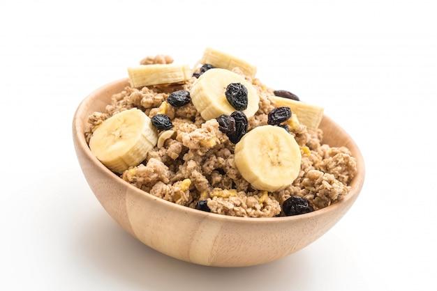 Muesli met banaan, rozijnen en melk voor het ontbijt