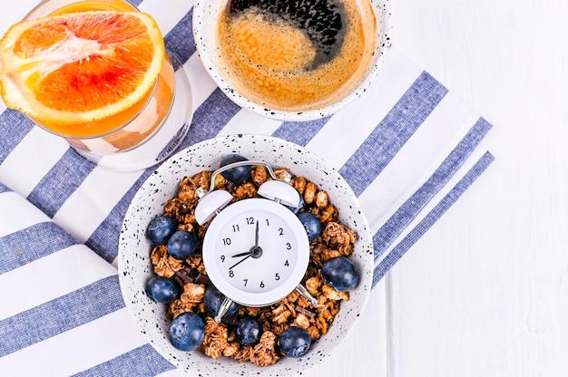 Muesli met bosbessen in een kop, jus d'orange en aromatische ochtendkoffie. ontbijt op een witte houten achtergrond en een wekker. plat leggen. kopieer ruimte