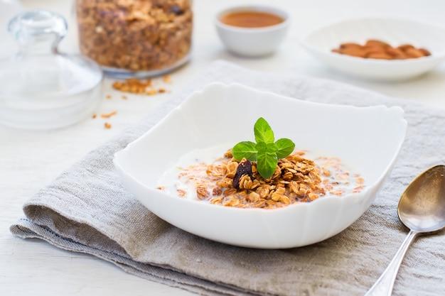 Muesli met melk, honing en noten op een witte tafel