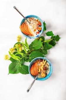 Muesli met melk, noten en vers fruit op een wit tafelkleed.