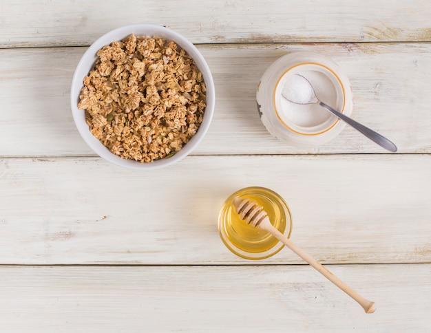 Muesli met pompoenpitten; melkpoeder in kruik en honing op houten tafel