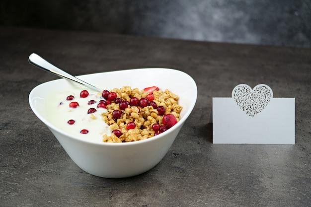 Muesli met srawberry en cranberry met yoghurt in witte kom op grijs