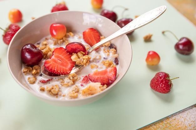 Muesli met vers fruit en yoghurt. pap met verse aardbeien en kersen