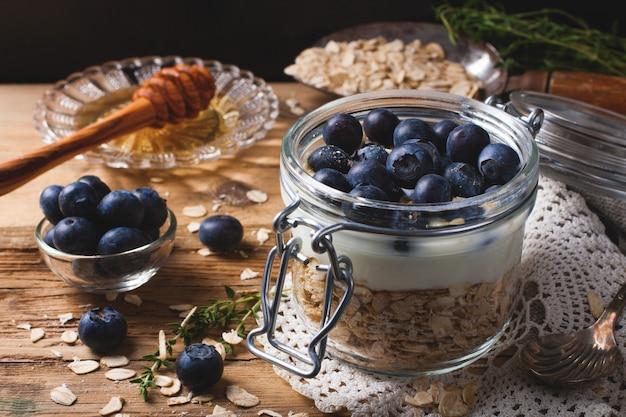 Muesli met yoghurt en blauwe bessen in glazen pot.