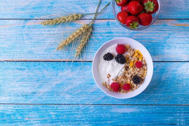 Muesli met yoghurt en fruit op houten tafel