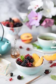 Muesli of muesli met bessen en fruit voor een gezond ontbijt in de ochtend met een boeket zomerbloemen op een lichte tafel.