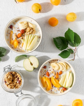 Muesliontbijt met fruit, noten, melk en pindakaas in kom. gezond ontbijt granen bovenaanzicht