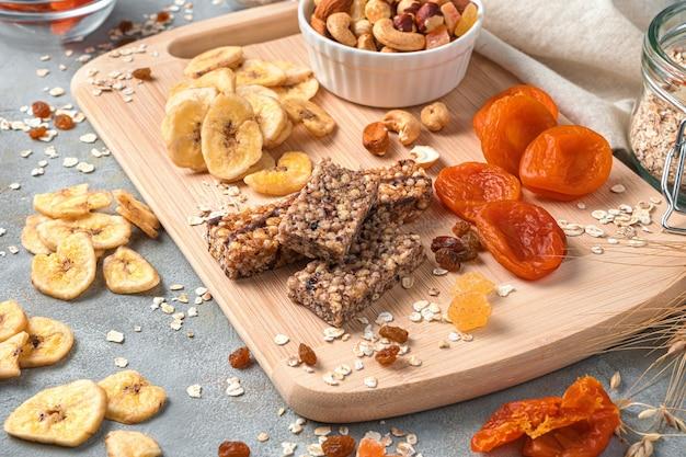 Mueslireep, gedroogde abrikozen, bananenchips, noten en gedroogd fruit op een bord op een grijze muur. gezond eten. zijaanzicht.