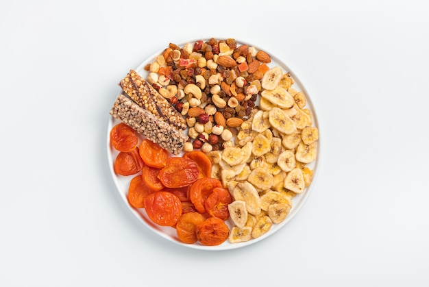 Mueslireep, gedroogde abrikozen, gedroogde bananen, noten en gedroogde vruchten in een witte vlakke plaat op een lichte muur. bovenaanzicht, horizontaal. gezond eten.