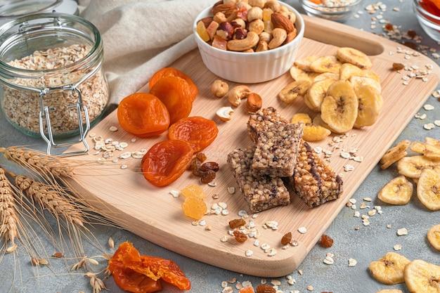 Mueslireep, gedroogde vruchten en noten op een snijplank op een grijze achtergrond.