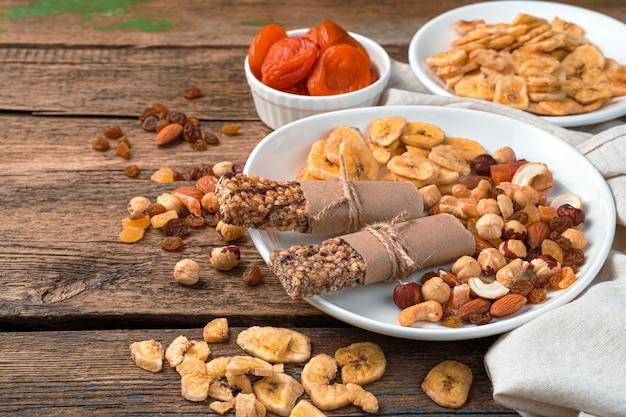 Mueslirepen, verschillende noten en gedroogde vruchten in een witte plaat op een houten muur. zijaanzicht, kopieer ruimte. gezonde snoepjes.