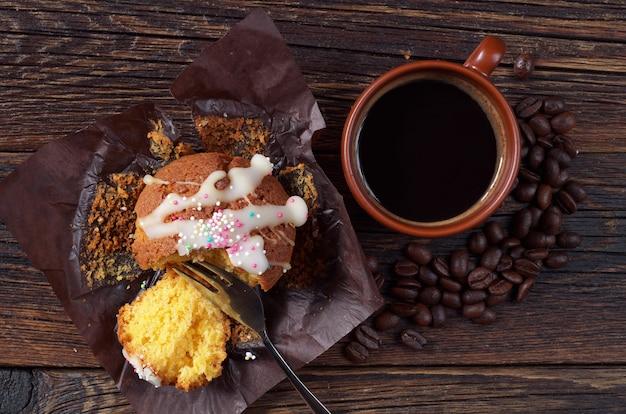 Muffin en plak in bruin papier met koffiekopje op donkere houten tafel, bovenaanzicht