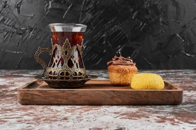 Muffin met drankje op een houten bord.
