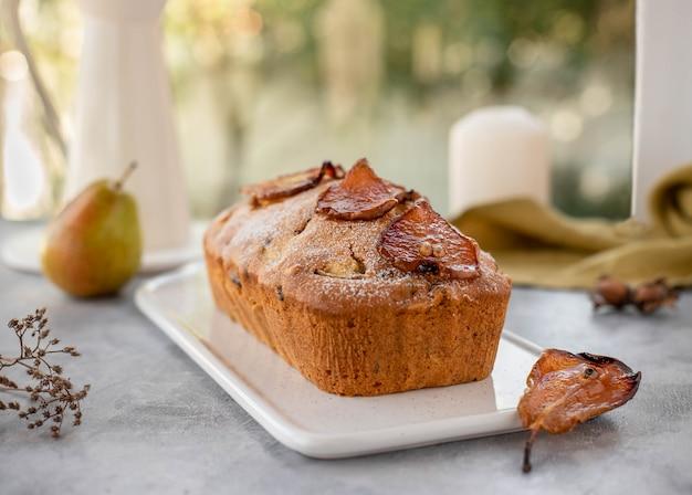 Muffincake met peren, noten versierd met gekarameliseerde peren.