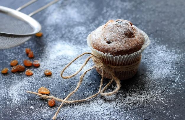 Muffins bestrooid met de poedersuiker op zwarte achtergrond