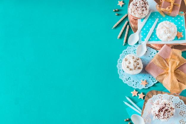 Muffins; cadeau- en verjaardagstoebehoren op groene achtergrond