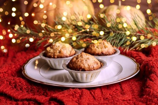 Muffins, cakes met noten op achtergrondruimte die voor kerstmis wordt verfraaid.