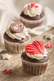 Muffins en chocolade en rode hartvormige snoepjes op een houten achtergrond.