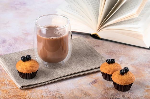 Muffins en glas witte koffie op tafel. warme drank, cacao en open boek.