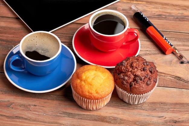 Muffins en kopjes koffie. lippenstift en eyeliner op hout. maak een heerlijke rem.