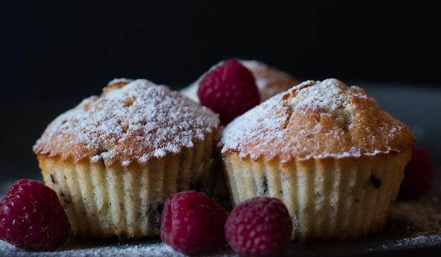 Muffins liggen op tafel met frambozen en poedersuiker