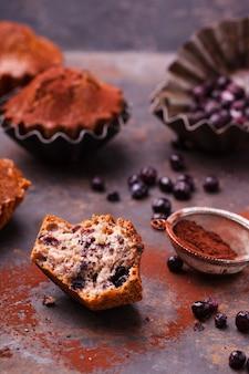Muffins met bosbessen, gegarneerd met cacaopoeder, op een donkere achtergrond.