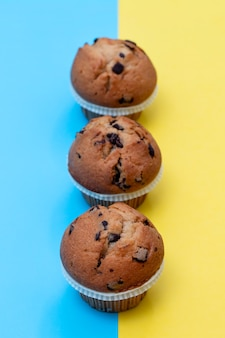 Muffins met chocolade op blauwe en gele achtergrond