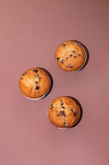 Muffins met chocolade op witte schotel op document achtergrond