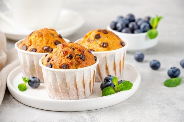 Muffins met chocoladeschilfers op een wit bord met kopje koffie en verse bosbessen