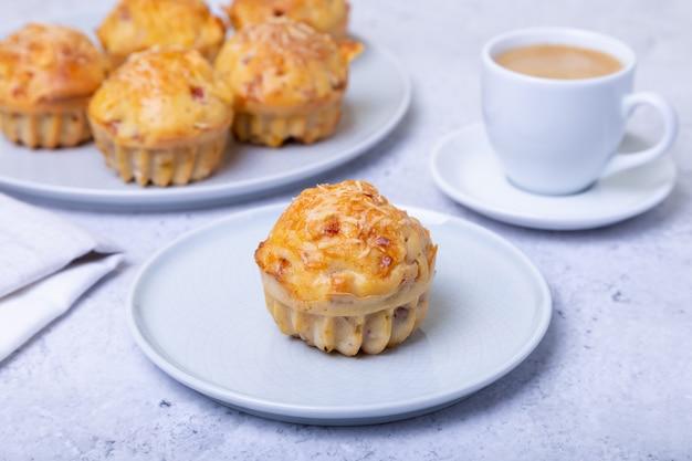 Muffins met ham en kaas. zelfgemaakt bakken. op de achtergrond is een bord met muffins en een kopje koffie. detailopname.
