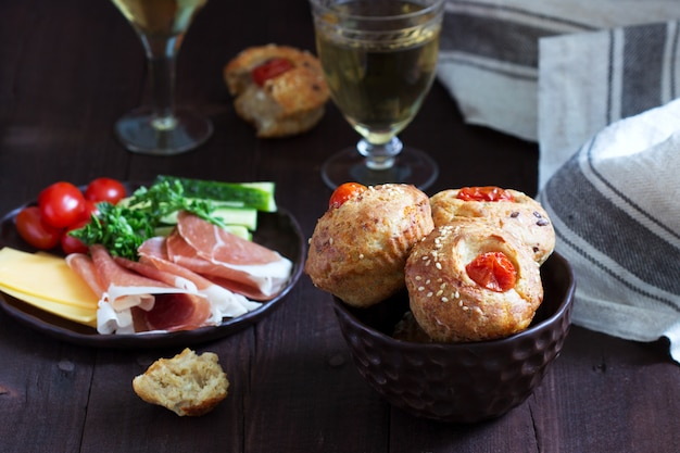 Muffins met kaas, kwark en tomaten, groenten en kaas geserveerd met wijn.