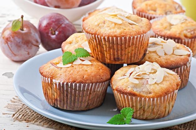 Muffins met pruimen en amandelbloemblaadjes versierd met muntblaadjes