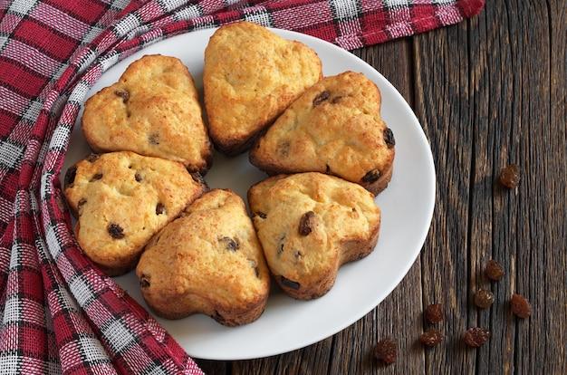 Muffins met rozijnen in de vorm van harten op rustieke houten tafel