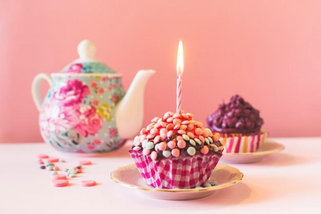 Muffins met verlichte kaars op verjaardag