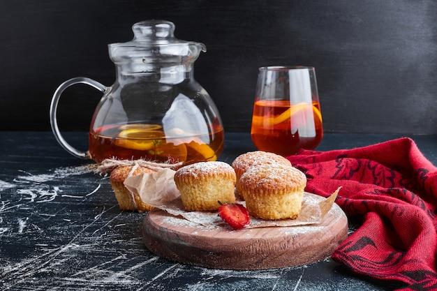 Muffins op een houten bord met een glas drank.