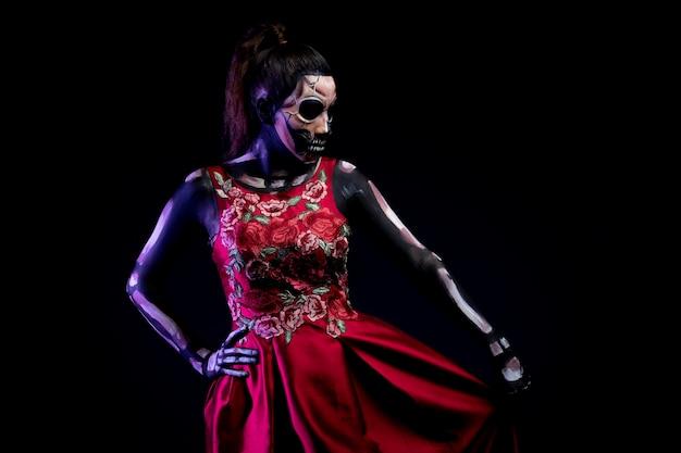 Mujer con body paint de calavera met vestido rojo en fondo azul por dia de muertos
