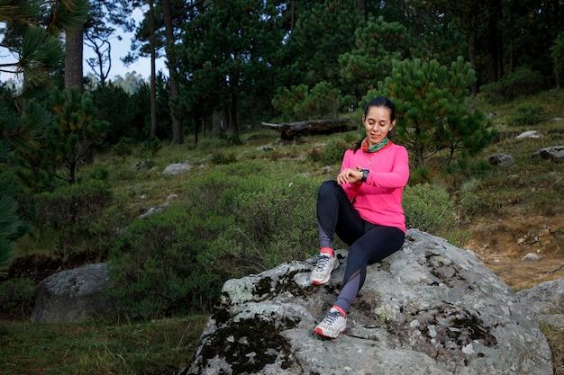 Mujer corredora usando su reloj inteligente despues de correr sentada en la orilla del lago