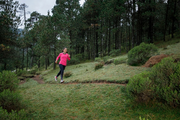 Mujer corriendo en un sendero del bosque con arboles al fondo