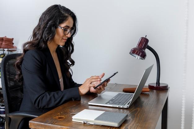 Mujer de negocios trabajando en casa y enviando mensajes con su celular