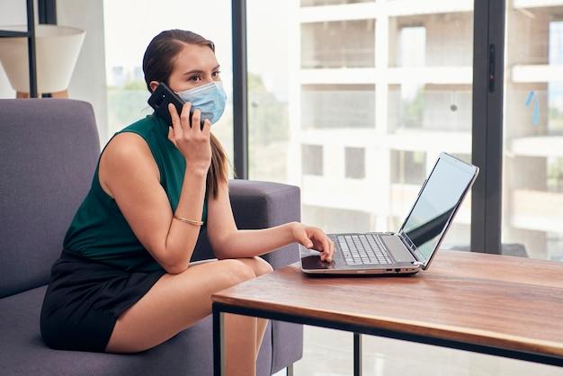 Mujer latina con cubrebocas hablando por celular mientras trabaja en casa