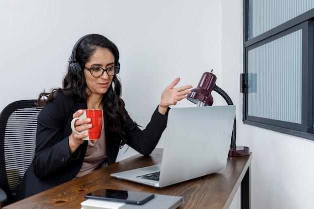 Mujer latina discutiendo en video conferencia trabajando en casa