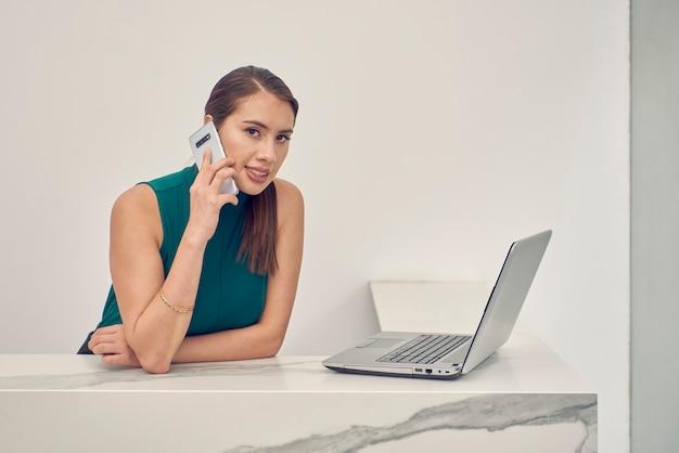 Mujer latina hablando por telefono mientras trabaja en su laptop