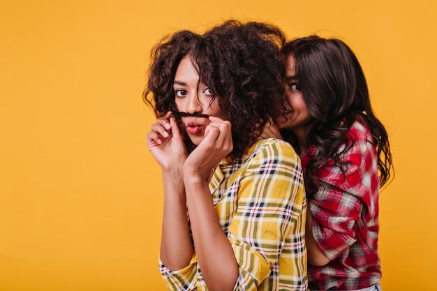 Mulat speelt met haar, snor maken van streng, terwijl haar vriend zich achter haar rug verstopt. portret van vrolijke meisjes die pret hebben.