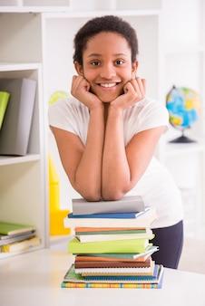 Mulatschoolmeisje die zich met stapel boeken bevinden.